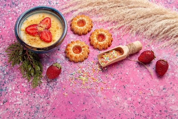 밝은 분홍색 배경에 빨간색 슬라이스 딸기와 쿠키가있는 상위 뷰 맛있는 크림 디저트 디저트 아이스크림 크림 달콤한 베리 과일