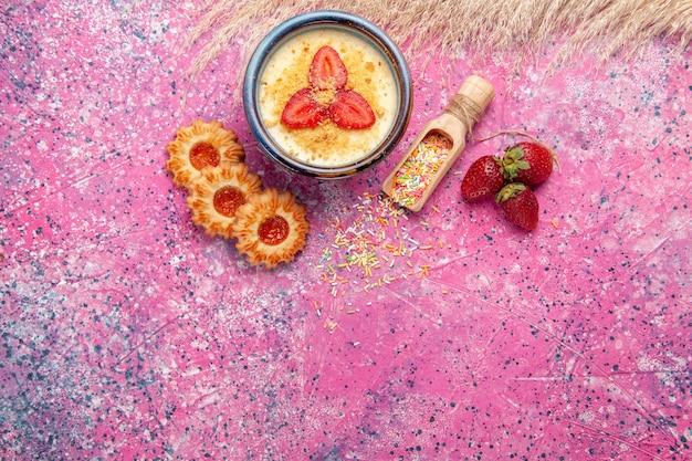 빨간 슬라이스 딸기와 밝은 분홍색 배경에 작은 쿠키가있는 상위 뷰 맛있는 크림 디저트 디저트 아이스크림 베리 크림 달콤한 과일