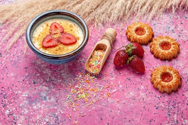 빨간 슬라이스 딸기와 밝은 분홍색 배경에 작은 쿠키가있는 상위 뷰 맛있는 크림 디저트 디저트 아이스크림 크림 달콤한 과일