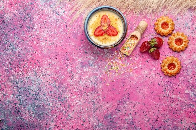 밝은 분홍색 책상에 빨간 슬라이스 딸기와 작은 쿠키가있는 상위 뷰 맛있는 크림 디저트 디저트 아이스크림 베리 크림 달콤한 과일