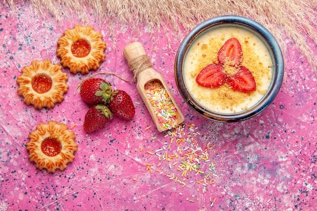 빨간 슬라이스 딸기와 밝은 분홍색 바닥에 작은 쿠키가있는 맛있는 크림 디저트 디저트 아이스크림 베리 크림 달콤한 과일