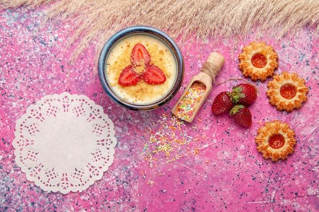 밝은 분홍색 배경에 빨간 슬라이스 딸기와 작은 쿠키가있는 상위 뷰 맛있는 크림 디저트 디저트 아이스크림 베리 크림 달콤한 과일