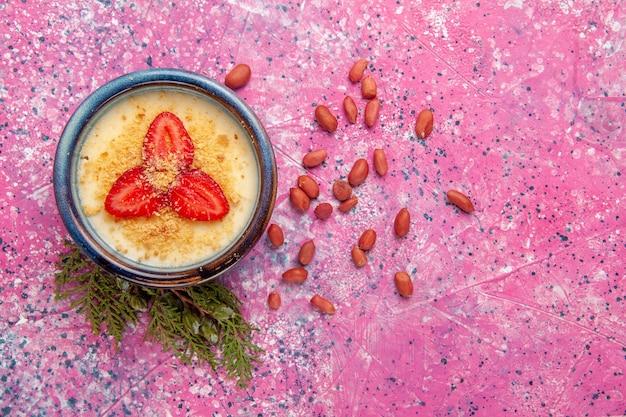 Вид сверху вкусный сливочный десерт с красной нарезанной клубникой и орехами на светло-розовом фоне десертное мороженое кремового цвета сладкие ягоды фруктов