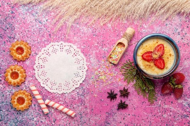 Vista dall'alto delizioso dessert cremoso con fragole rosse a fette e biscotti su sfondo rosa chiaro dessert gelato alla crema di frutti di bosco frutta dolce