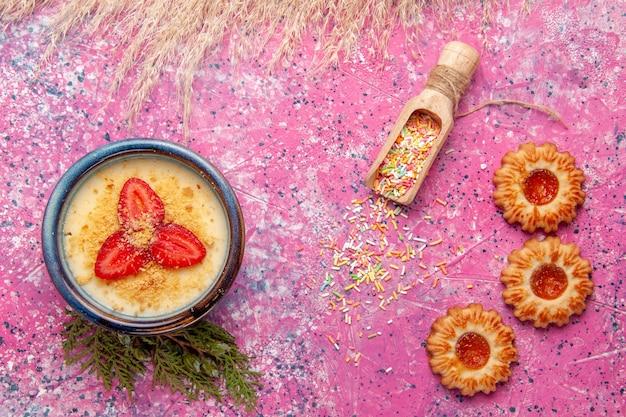 Vista dall'alto delizioso dessert cremoso con fragole rosse a fette e biscotti su sfondo rosa chiaro dessert gelato crema di frutti di bosco dolci