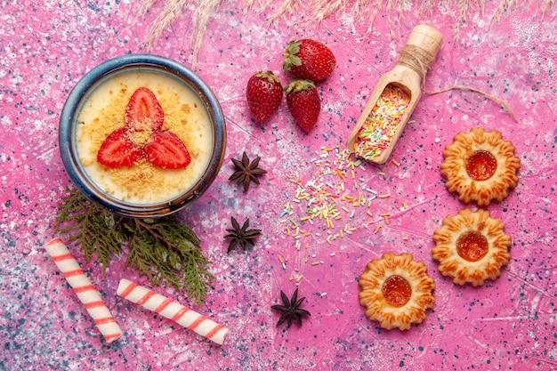 Vista dall'alto delizioso dessert cremoso con fragole rosse a fette e biscotti su frutta a bacca dolce crema dessert gelato da scrivania rosa chiaro