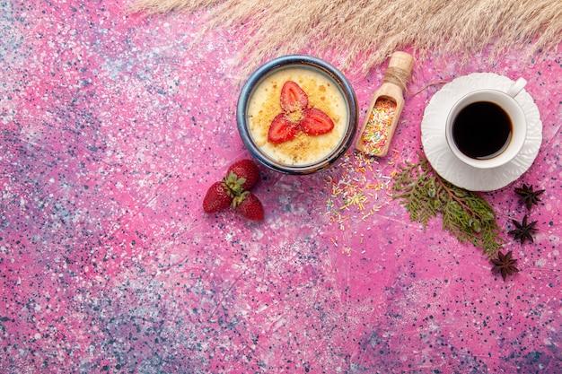 Vista dall'alto delizioso dessert cremoso con fragole rosse a fette e tazza di tè sullo sfondo rosa chiaro dessert gelato alla crema di bacche frutta dolce