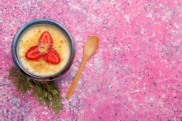 平面図のおいしいクリーミーなデザート、ライトピンクの背景のプレートの内側に赤いスライスしたイチゴのデザートアイスクリームクリーム色の甘いフルーツベリー