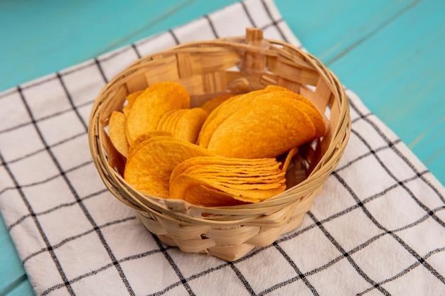Vista dall'alto di deliziose patatine croccanti su un secchio su un panno controllato