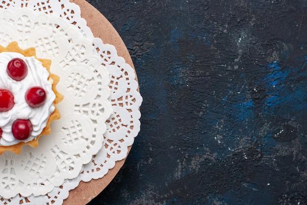 Vista dall'alto deliziosa torta d con crema e frutti rossi sul biscotto di frutta torta superficie scura