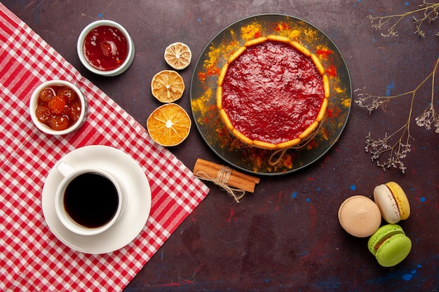トップビューダークデスクにコーヒーマカロンとフルーツジャムのカップが付いたおいしいデザートケーキビスケットシュガークッキーケーキデザートスイート