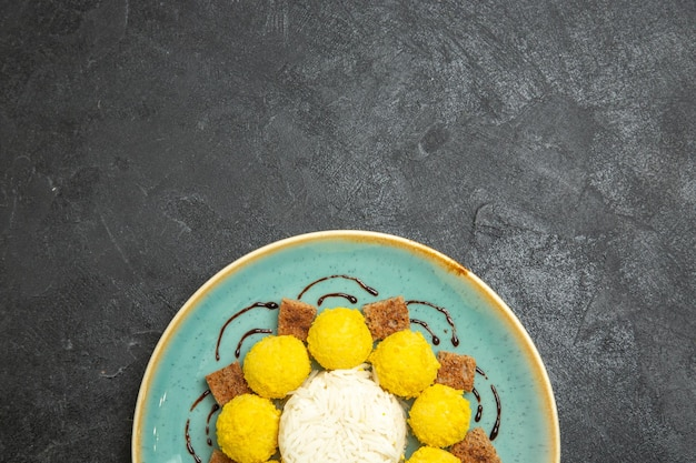 Top view delicious dessert little yellow candies with cake inside plate on dark grey background candy tea sugar cake sweet