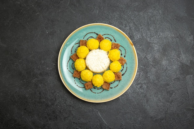 Top view delicious dessert little yellow candies with cake inside plate on a grey background candy tea sugar cake sweet