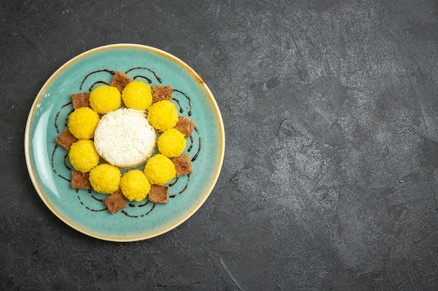 Top view delicious dessert little yellow candies with cake inside plate on the grey background candy tea sugar cake sweet