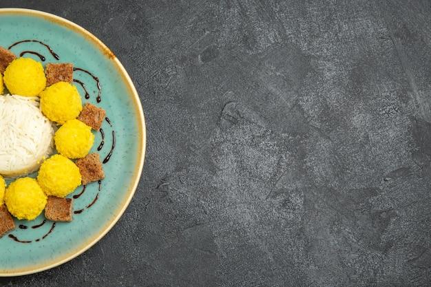 Вид сверху вкусный десерт маленькие желтые конфеты с тортом внутри тарелки на сером столе конфеты чай сахарный торт сладкий