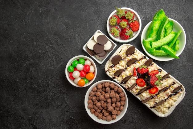 Вид сверху вкусный десерт с конфетами, печеньем и клубникой на темном фоне, ореховое печенье, сладкое фруктовое печенье, сахар