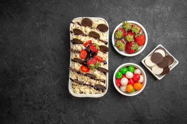 Вид сверху вкусный десерт с шоколадным печеньем, конфетами и клубникой на темном фоне, ореховое печенье, сладкое фруктовое печенье, сахар