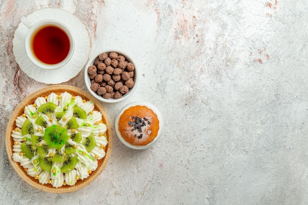 スライスしたキウイと白い背景の上のお茶のトップビューおいしいデザートビスケットクリームフルーツデザートキャンディーケーキ