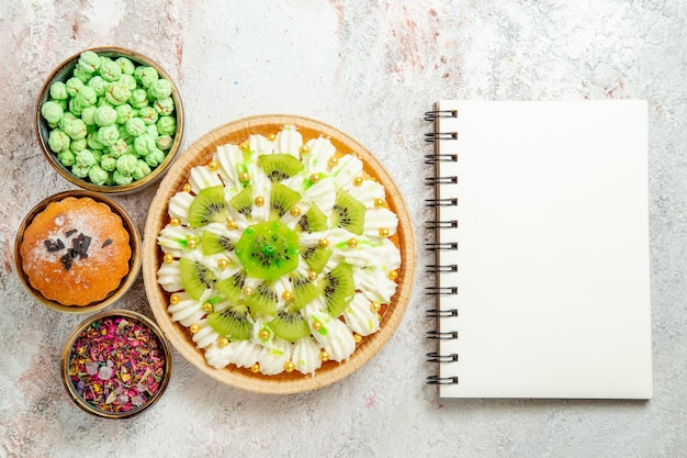 Top view delicious dessert with sliced kiwis and candies on a white background cake biscuit dessert cream fruit candy