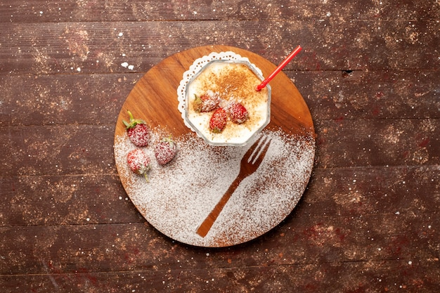 Vista dall'alto delizioso dessert con fragole sulla scrivania marrone