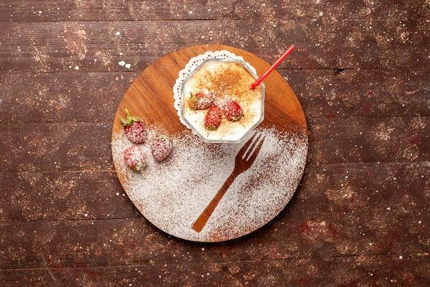 茶色の机の上にイチゴとトップビューのおいしいデザート