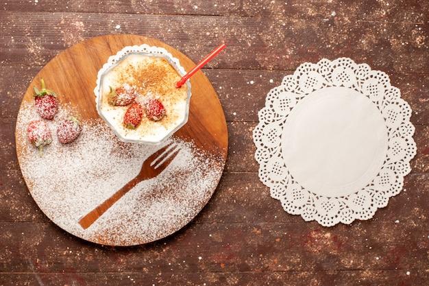 茶色の木製の机の上にイチゴとトップビューのおいしいデザート
