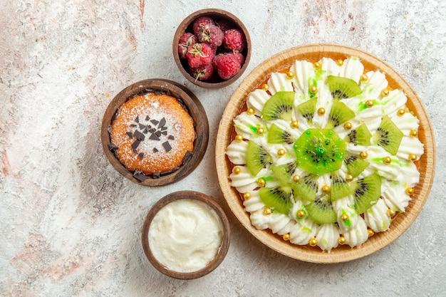 上面図白い背景の上の白いクリームとおいしいデザートデザートクリームフルーツケーキキャンディー