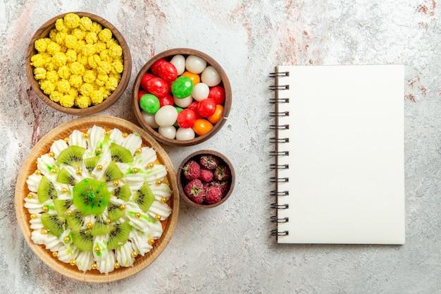 Vista dall'alto delizioso dessert con crema bianca e kiwi a fette su fondo bianco torta alla crema di frutta frutta