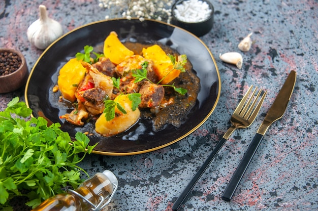Vista dall'alto di una deliziosa cena con patate a base di carne servite con verde in un piatto nero e aglio spezie bottiglia di olio caduta fiore posate impostato su sfondo colori mix