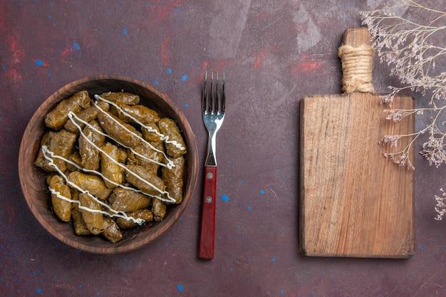 Вид сверху вкусное восточное мясное блюдо долма с листьями и фаршем на темном столе еда калорийность обед масло блюдо мясо