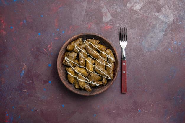 Vista dall'alto delizioso piatto di carne orientale dolma con foglie e carne macinata sullo sfondo scuro cibo calorico cena olio piatto carne