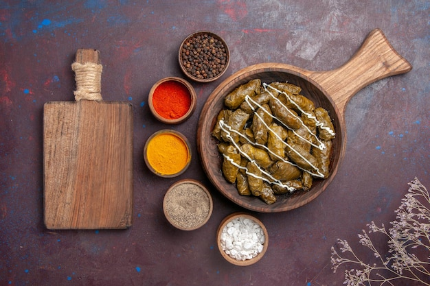 Top view delicious dolma meat dish with different seasonings on a dark background food calorie dinner dish meat