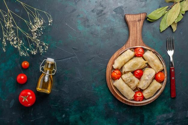 Вид сверху вкусной мясной муки долмы, рулет из капусты и помидоров вместе с оливковым маслом на темно-синем столе мясная еда ужин овощи приготовление блюда