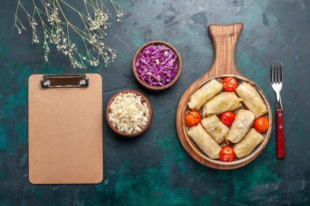 Вид сверху вкусной мясной муки долмы, свернутой с капустой и помидорами на темно-синем столе, мясная еда, ужин, овощи, приготовление блюда
