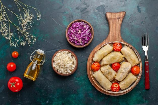Vista dall'alto deliziosa farina di carne dolma arrotolata con cavolo e pomodori insieme ad olio sulla scrivania blu scuro carne cibo cena verdure piatto da cucina