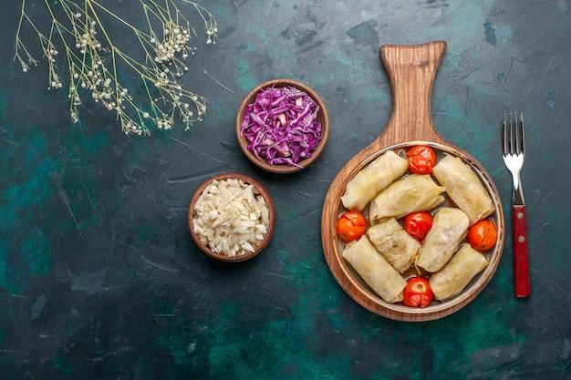 Vista dall'alto delizioso dolma farina di carne arrotolata con cavolo e pomodori sulla scrivania blu scuro carne cibo cena verdure piatto di cottura