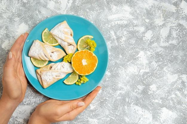 상위 뷰 흰색 배경에 레몬 조각으로 맛있는 반죽 파이 과자 설탕 빵 케이크 반죽 달콤한 파이 쿠키