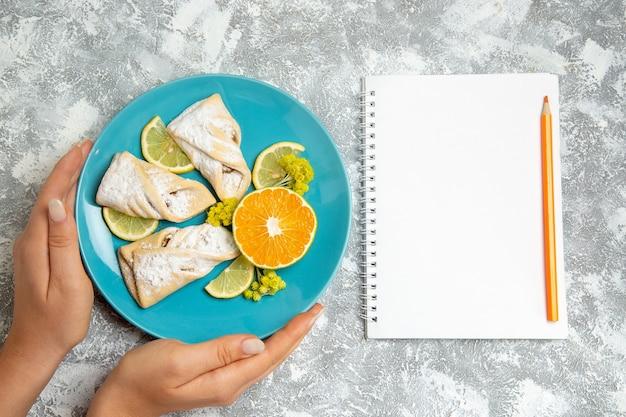 Vista dall'alto deliziosi pasticcini di pasta con fette di limone sulla scrivania bianca pasticceria zucchero cuocere torta pasta dolce torta