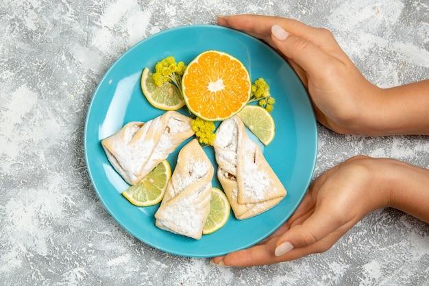 Vista dall'alto deliziosi pasticcini della pasta con fette di limone sulla superficie bianca pasticceria zucchero cuocere la torta pasta torta dolce biscotti