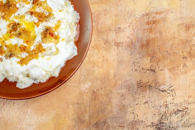 Vista dall'alto deliziose fette di pasta con yogurt e olio su superficie chiara