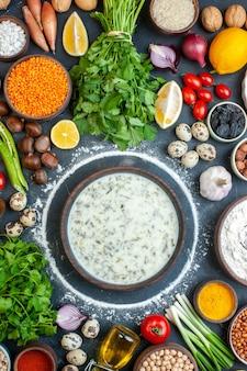 Vista dall'alto deliziosa dovga in una ciotola di legno coriandolo pomodorini uova di quaglia aglio e altre cose sul tavolo