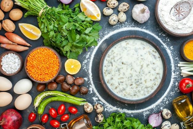 Vista dall'alto deliziosa dovga in una ciotola di legno coriandolo pomodorini uova di quaglia aglio noce castagna sul tavolo