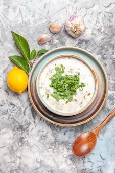 Vista dall'alto deliziosa zuppa di yogurt dovga con verdure su piatto da tavola bianco per zuppa di latte