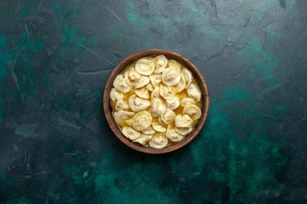 Vista dall'alto deliziosa zuppa di gnocchi all'interno del piatto marrone su sfondo verde scuro pasta alimentare zuppa di verdure carne