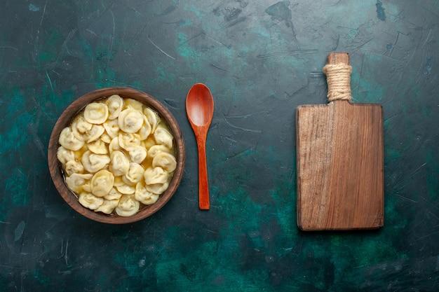 Vista dall'alto una deliziosa zuppa di gnocchi all'interno del piatto marrone sul pavimento verde scuro, carne, verdura, zuppa, pasta