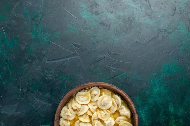 濃い緑色の背景に茶色のプレート内のおいしい餃子スープの上面図食品野菜スープ肉生地