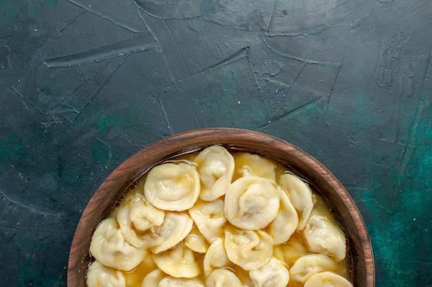 濃い緑色の床の茶色のプレートの内側のおいしい餃子スープの上面図食品生地野菜スープ肉