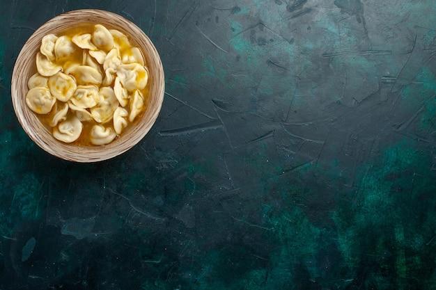 濃い緑色の背景においしい餃子スープの上面図食品生地肉野菜スープ