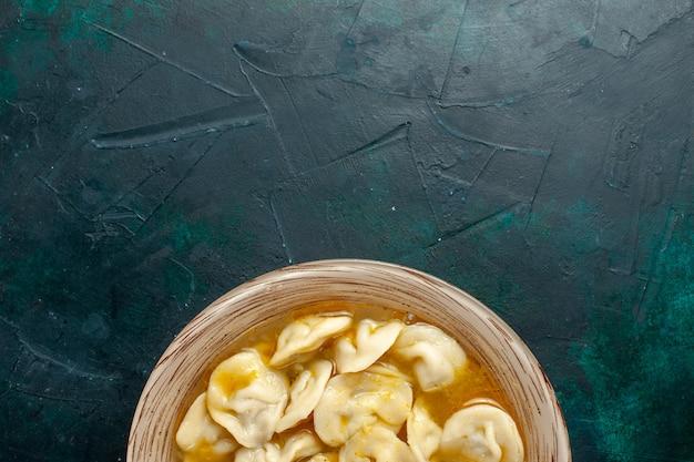 濃い緑色の背景においしい餃子スープの上面図食品生地野菜スープ肉