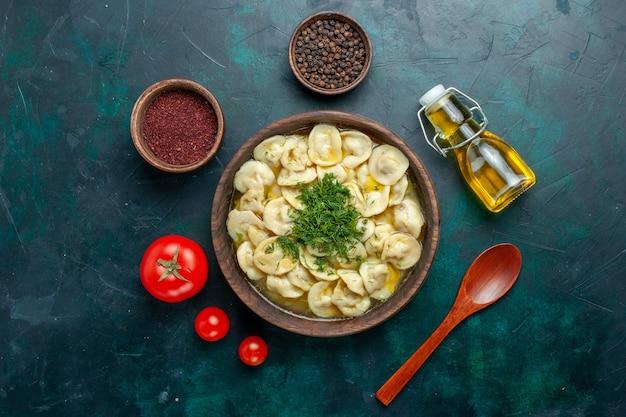Vista dall'alto deliziosa zuppa di gnocchi con diversi condimenti su una zuppa di pasta alimentare vegetale di carne da scrivania verde scuro